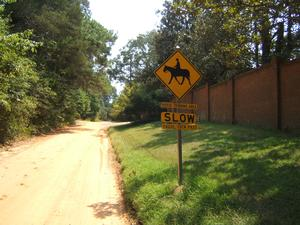 Non paved road in historic horse district with sign for vehicle traffic when meeting horses